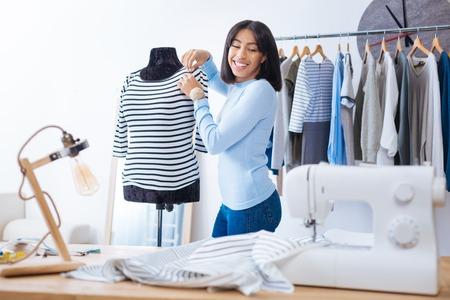Blij zijn. Positieve jong ervaren kleermaker die zich dichtbij de ledenpop bevindt en glimlacht terwijl het bekijken de nieuwe naaimachine