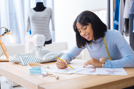 Lovely sketches. Cheerful young creative worker of a fashionable atelier looking happy while sitting at the table and drawing a sketch for future clothes Stock Photo