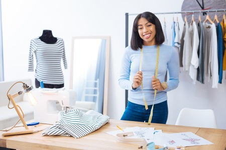 Preparation. Positive worker of a professional atelier standing with a yellow tape measurer on her neck and smiling while getting ready for a new working day