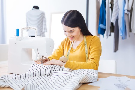 Working day. Calm qualified experienced tailor sitting at her working place and looking attentive while sewing a new lovely striped blouse