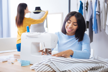 Different activities. Cheerful enthusiastic smiling tailor sitting at the table and sewing while her younger colleague standing behind her back and measuring a new blouse Stock Photo