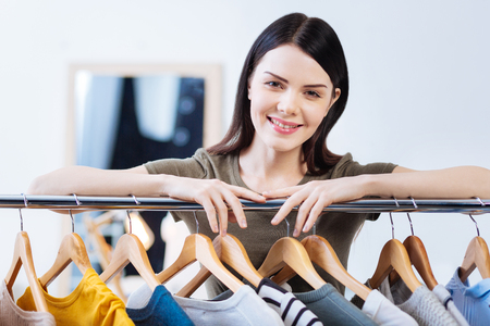 Peaceful smile. Polite young pretty woman standing in a fashionable atelier and smiling while her hands touching a convenient clothes rail Stock Photo