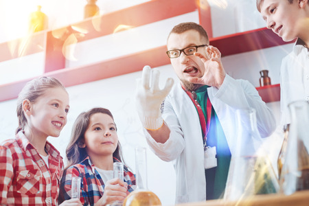 Who said science had to be boring. Young future chemists with a rapturous glance watching their hilarious and very emotional male teacher entertaining them with funny faces during a chemistry lesson.
