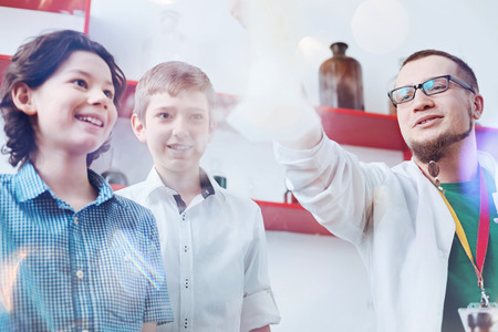 Never get bored. Two amazed boys looking at a fuming laboratory flask held by a male up and coming chemist wearing a laboratory coat and glasses. Stock Photo