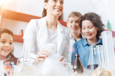 Science is fun. Happy boys and a girls smiling while taking part in a practical session held by their chemistry teacher in the school laboratory. Stock Photo