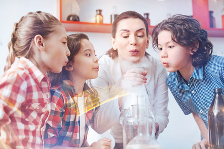 Work in team. Female chemistry teacher conducting a practical lesson with her pupils and involving them in the process of performing a chemical experiment. Stock Photo