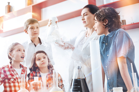 Can you see the reaction. Amazed up and coming chemists looking at a chemical reaction in a fuming filter flask held by a teacher of chemistry wearing a laboratory coat.