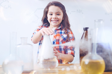 So excited to learn new things. Elementary female student grinning broadly while working with a chemistry set and conducting an experiment during a chemistry lesson. Stock Photo