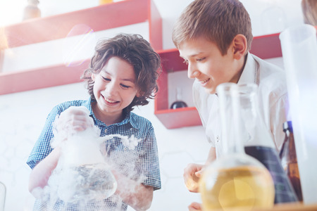 Future scientists. Happy boys standing in the laboratory and holding a fuming vacuum flask while working on a school project during a chemistry lesson.