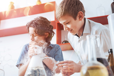 Experimenting in the laboratory. Smart schoolboys both wearing shirts looking at a fuming flask while performing an experiment with different liquids in the school laboratory.