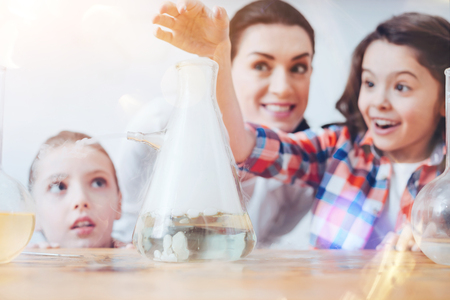 Creative chemistry. Future female scientists using a filter flask while participating in a chemical experiment held by a teacher wearing a laboratory coat at school. Stock Photo