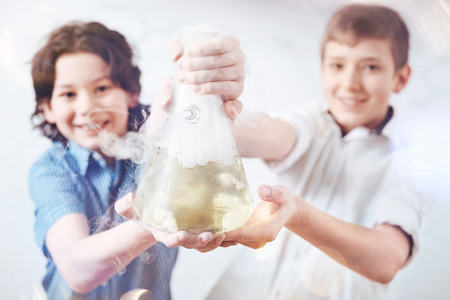 Up and coming chemists. Selective focus on a fuming filter laboratory flask held by a group of two positive future chemists posing together and smiling into the camera.