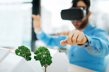Modern approach. Bristled young architect sitting at the work desk in the office and pointing at tree models being in the focus while wearing a VR headset Фото со стока