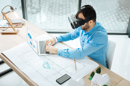 Engaged at work. The top view of a bristled young architect wearing a VR headset and working on a laptop while sitting at the work desk with a blueprint on it