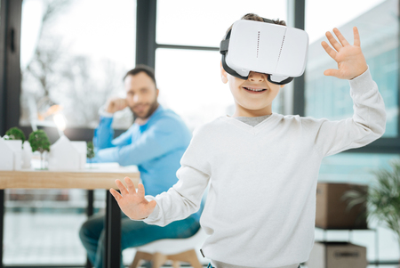 Interesting pastime. Adorable little boy trying out a new VR headset and raising his hands, moving in a virtual reality, while his father sitting at the work desk and looking at him Stock Photo