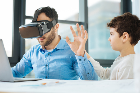Gentle touch. Charming little boy approaching his father and touching his back while the man sitting at the table and testing a VR headset