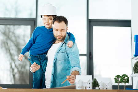 Best work companion. Charming young man holding his little son in a hard hat while standing near his work desk and finishing up a blueprint
