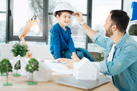Gentle care. Pleasant loving father adjusting a hard hat on the head of his little son sitting on the table in fathers office while the man working on a blueprint