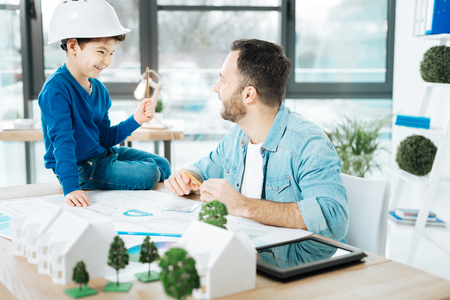Exciting conversation. Adorable little boy in a hard hat sitting on the table and chatting with his father about his work while holding a pencil in his hand