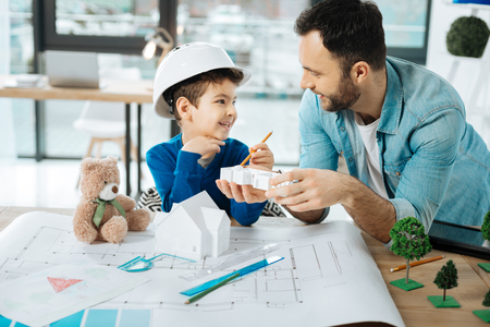 Interesting discoveries. Cheerful little boy in a hard hat and his loving father sitting in the office and examining the models of constructions Stock Photo