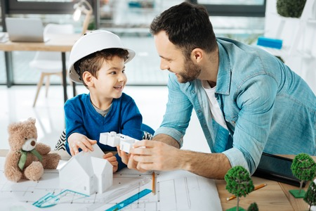 New information. Pleasant young father and his little son in a white hard hat standing in the office near the table and discussing a 3D house model Stock Photo