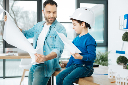 Skilled artists. Cute little boy in a white hard hat holding a picture while sitting on the table next to his father showing a blueprint to him Stock Photo