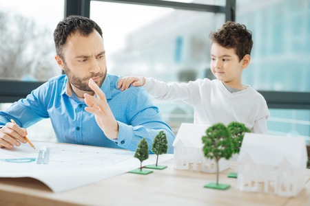 Do not disturb. Chubby little boy disturbing his father by touching his back while he working on a blueprint in the office Stock Photo