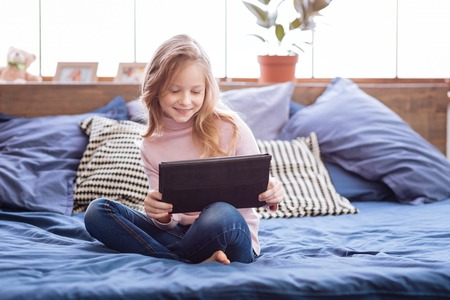 Spare time. Lovely joyful fair-haired girl smiling and playing games on her tablet while sitting on the bed