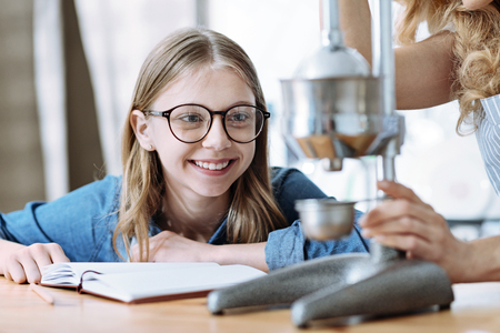 Delighted little female that expressing positivity and being in glasses while leaning on table Stock Photo