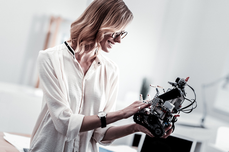 It is new. Confident female expressing positivity while looking at robot and thinking about future