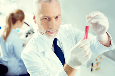 Top view on a bearded man looking into the camera while standing in a laboratory and holding a test tube with a red chemical liquid. Stock Photo
