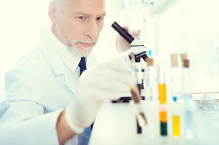 Selective focus on a serious mature laboratory worker sitting at a microscope and taking one of the test tubes containing chemical liquid. Stok Fotoğraf