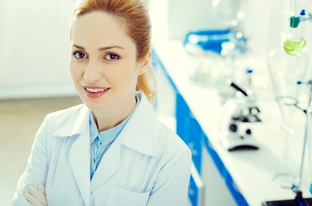 Top view on a joyful female scientist looking into the camera and smiling while standing in a lab.