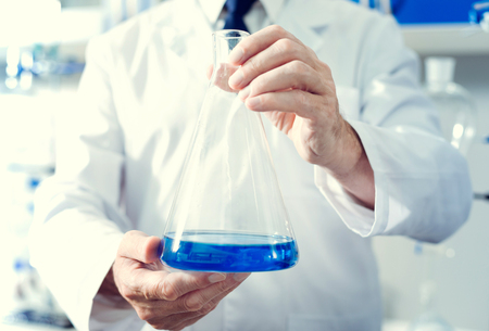 Professional equipment. Scaled up look on a mature gentleman wearing a labcoat holding a flask with a navy blue chemical liquid while standing in a lab.