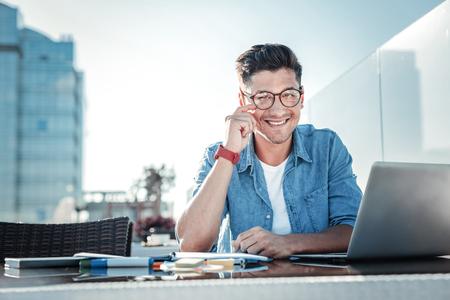 la cintura tiró de un hombre mayor alegre del libro sentado en su computadora portátil y mirando a la cámara con una sonrisa grande en la cara mientras que trabaja en un café Foto de archivo