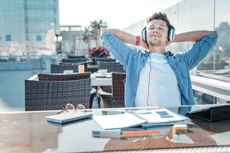 Joyful self employed gentleman in casual holding hands behind his head and smiling while listening to music after working long hours outdoors. Stock Photo