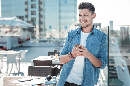 Cheerful guy grinning broadly while leaning on a glass fence and using his smartphone in a local cafe.