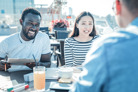 Best mates forever. Positive minded young friends having fun together and smiling cheerfully while meeting in a local cafe for a lunch. Stock Photo