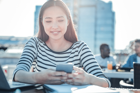 Reading news. Relaxed young lady enjoying her free time and smiling while sitting outdoors and browsing the Internet on her smartphone.