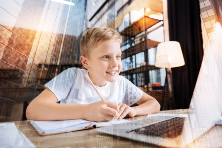 Cheerful clever boy sitting in front of a modern laptop and smiling while holding a pen and doing his homework