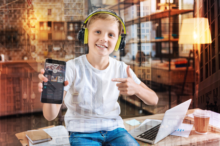 Cheerful clever progressive boy smiling and sitting on the table while listening to his favorite song in big headphones Stock Photo