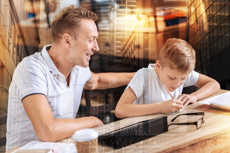 Positive delighted father sitting in semi position and cheering up his son, keeping smile on his face Stock Photo