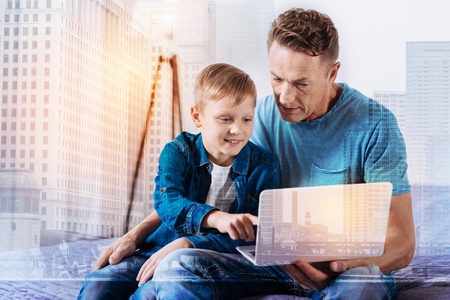 Positive delighted boy keeping smile on his face and leaning himself on daddy while pointing at computer