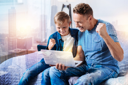Online communication. Handsome man expressing positivity while looking at computer and sitting near his kid Stock Photo