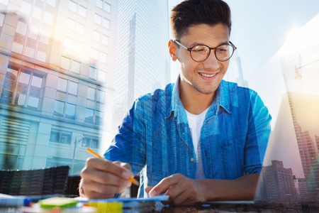 In high spirits. Handsome exuberant young man wearing glasses and holding a pencil and smiling Stok Fotoğraf