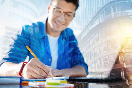 Taking notes. Handsome alert young man wearing glasses and writing in his notebook and smiling