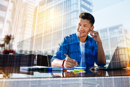 Thoughts. Good-looking inspired young man smiling and holding a pencil and thinking while working on his laptop