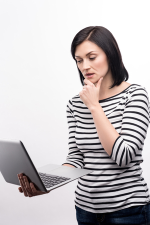 Deep in thoughts. Beautiful dark-haired young woman holding a laptop and reading from it, touching her chin, while standing isolated on a white background Stock Photo