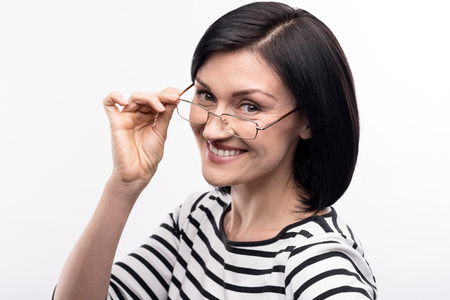 Enchanting smile. The portrait of a pleasant young dark-haired woman posing for the camera and touching the rim of her eyeglasses while standing half-turned Stock Photo