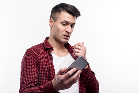 Praising ego. Well-built charming man in a check shirt holding his phone and taking selfies while standing isolated on a white background